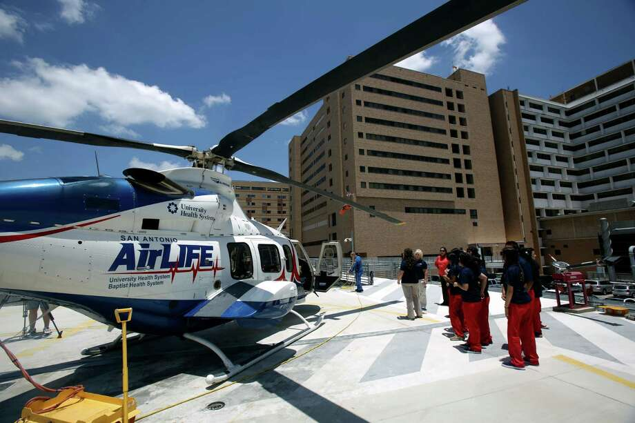 Participants in Camp 98.6 view the AirLIFE helicopter before the crew members head out to a call. About 15 students from Fox Tech Magnet High School participated in Camp 98.6, an intensive summer education program. Photo: Express-News File Photo / ©2013 San Antonio Express-News