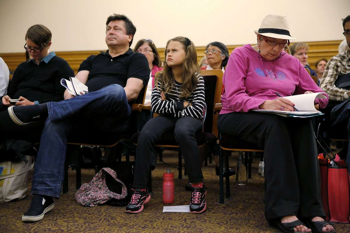 Eight-year-old Valentina Eibl (center) scowls at a city employee as he talks about a tree outside her house they plan to cut down during a public hearing regarding construction on Van Ness Avenue and the removal of nearly 200 trees in San Francisco, California, on Monday, Aug. 24, 2015.