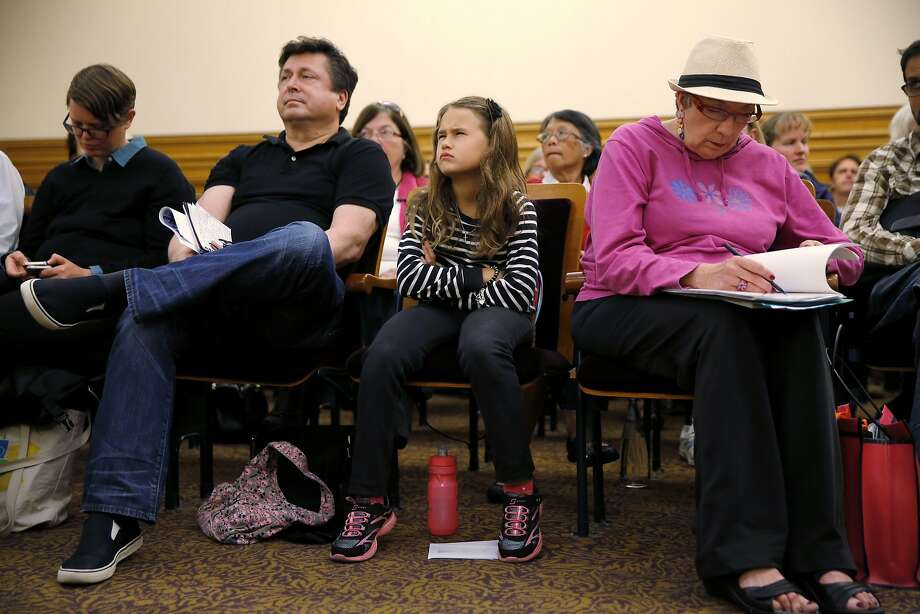 Valentina Eibl, 8, scowls as a city employee discusses plans to remove a tree outside her home. Photo: Connor Radnovich, The Chronicle