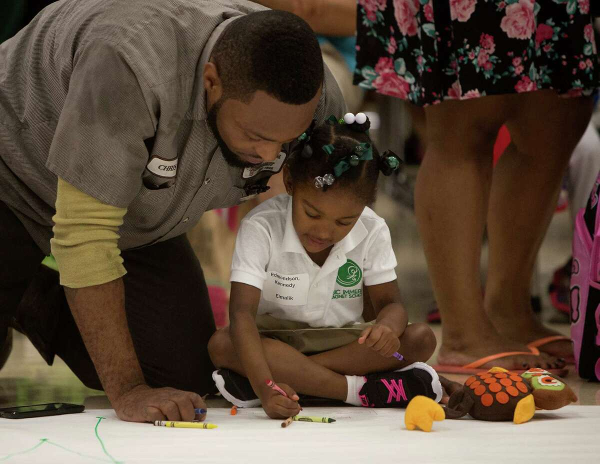 Chris Edmondson, left, colors with his daughter, Kennedy, 3, as they wait for school to start at the Arabic Immersion Magnet School, Monday, Aug. 24, 2015, in Houston.