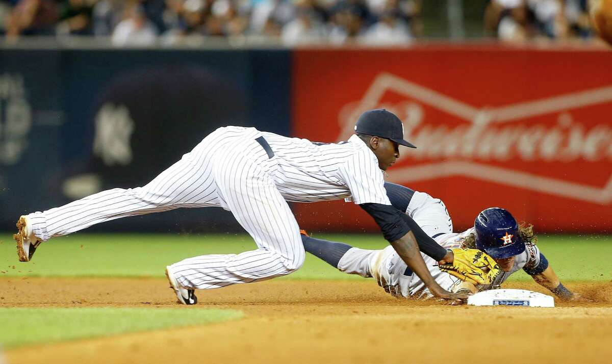 The Astros' Colby Rasmus, right, gets tagged out at second base in the sixth inning by the Yankees' Didi Gregorius on a fielder's choice grounder.