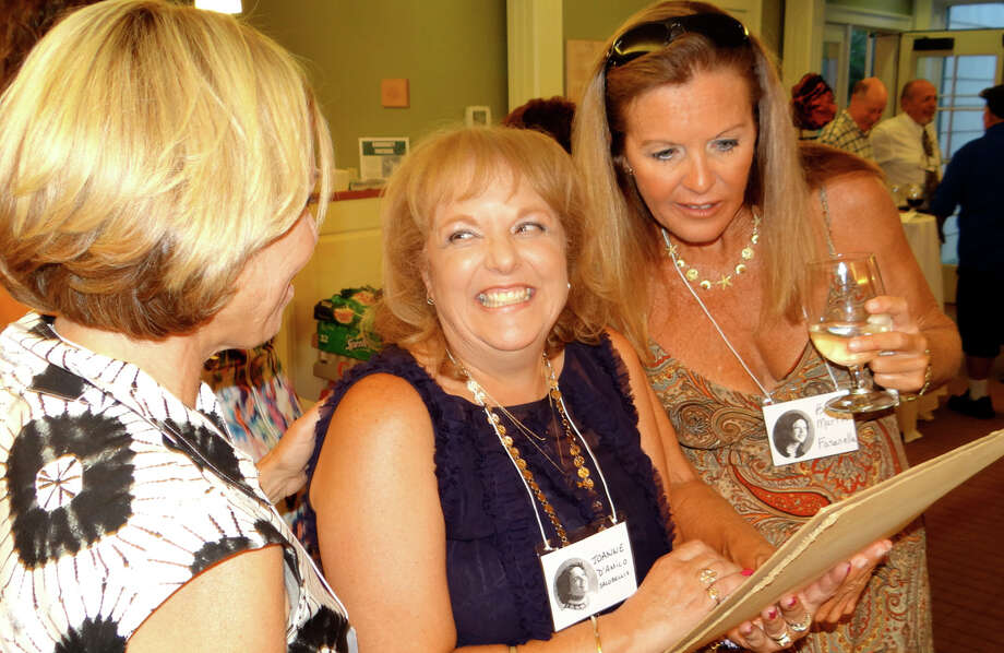 Sissy Cargill Biggers, Joanne D'Amico Jacobellis and Beth Martin Fasanella look at an old class photo at the Roger Ludlowe High School Class of 1975 reunion at the Fairfield Museum and History Center on Saturday evening. Photo: Mike Lauterborn / For Hearst Connecticut Media / Fairfield Citizen