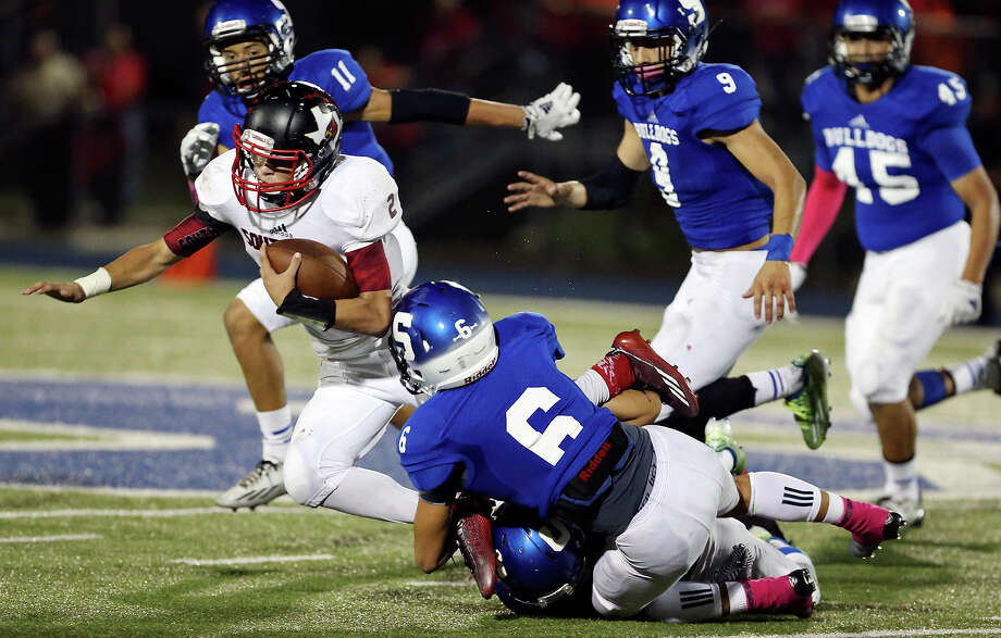 Southside's Matthew Collier (left) tries to shake the tackle of Somerset's Cory Isbell and Jonathan Guevarra during second half action on Oct. 10, 2014, at Bulldog Stadium in Somerset. Photo: Edward A. Ornelas /San Antonio Express-News / © 2014 San Antonio Express-News