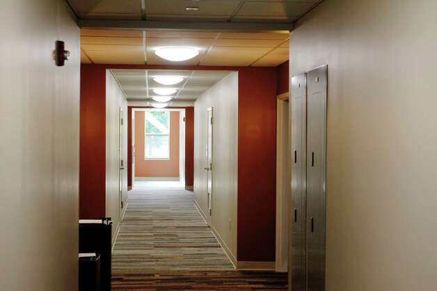 A view looking down the hallway at Garnet Commons, the new 80-bed apartment style residence hall at Union College, seen here on Tuesday, Aug. 25, 2015, in Schenectady, N.Y.  The building has 23 apartments broken into fully furnished four-, three-and two-bedroom units.  The building was completed in ten months and it filled up with students through the school's lottery system in 56 minutes.  The space design inside along with the color schemes and furniture were chosen by students through a voting system.  The building is a LEED Silver building.  Building features include a multi-purpose room, lounge, study room, meeting room and music room on the ground floor along with a laundry room.   (Paul Buckowski / Times Union) Photo: PAUL BUCKOWSKI / 00033103A