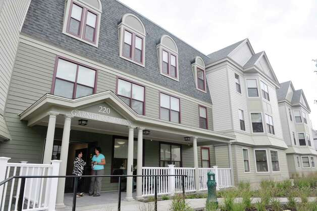Daria Mallin, background left, project manager for Envision Architects, and Amanda Bingel, Union College director of residential life, talk outside of Garnet Commons, the new 80-bed apartment style residence hall at Union College, seen here on Tuesday, Aug. 25, 2015, in Schenectady, N.Y.  Mallin was part of the architect team that worked on the building.  The building has 23 apartments broken into fully furnished four-, three-and two-bedroom units.  The building was completed in ten months and it filled up with students through the school's lottery system in 56 minutes.  The space design inside along with the color schemes and furniture were chosen by students through a voting system.  The building is a LEED Silver building.  Building features include a multi-purpose room, lounge, study room, meeting room and music room on the ground floor along with a laundry room.   (Paul Buckowski / Times Union) Photo: PAUL BUCKOWSKI / 00033103A