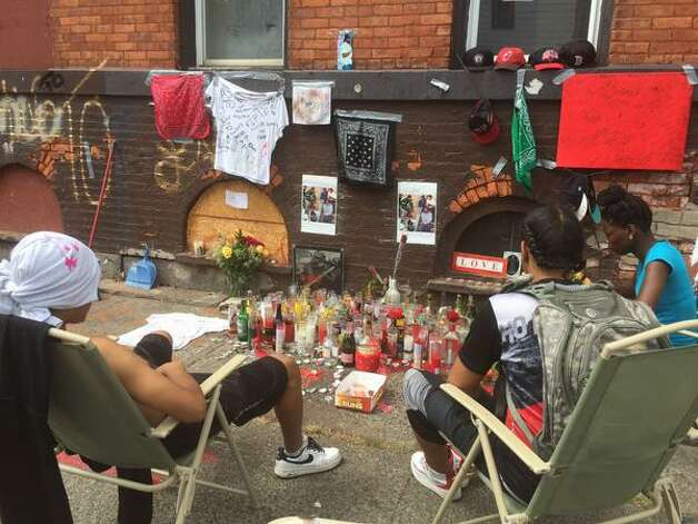 Friends sit by a memorial at Glen and 7th Avenue in Troy on Tuesday, Aug. 25, 2015, for Thaddeus Faison, who was killed in a shootout with police. (Lori Van Buren/Times Union)
