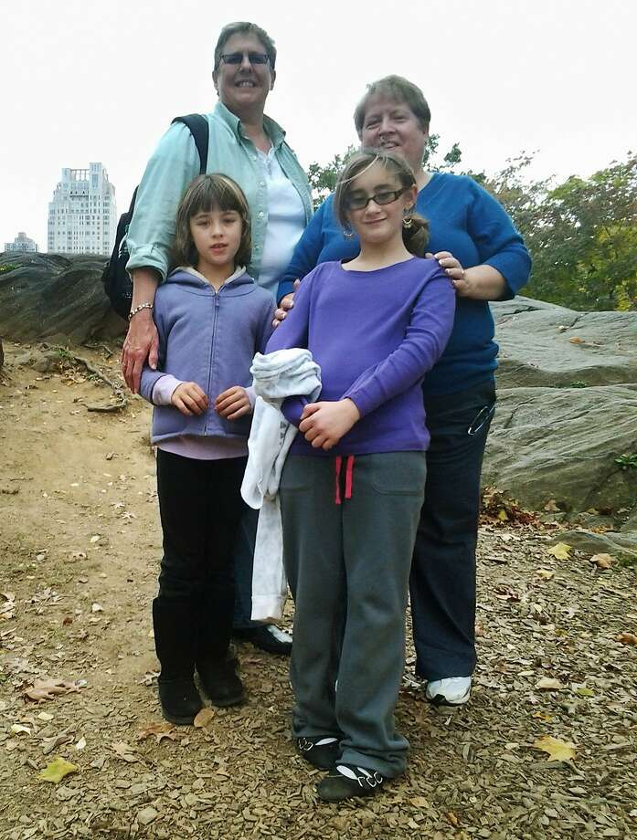 """This October 2012 photo provided by Marianne Duddy-Burke shows her, background right, with her wife, Becky Duddy-Burke and their daughters Infinity, foreground left, and Emily in New York's Central Park. Marianne, executive director of the LGBT Catholic group Dignity USA, has planned to attend the September 2015 World Meeting of Families in Philadelphia with her family. """"We want to be a visible presence, with the message that LGBT families are part of the church,"""" she says. """"I would expect most people who are coming have LGBT family members ... Most of them are going to recognize that what the church teaches is harmful."""" (Marianne Duddy-Burke via AP) Photo: Associated Press"""