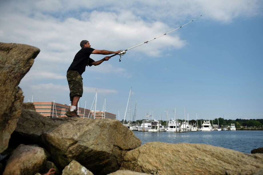 George Gomez, of Stamford, takes advantage of the summer weather by fishing off the rocks overlooking Long Island Sound at Kosciuszko Park in Stamford. Photo: Tyler Sizemore / Hearst Connecticut Media / Greenwich Time