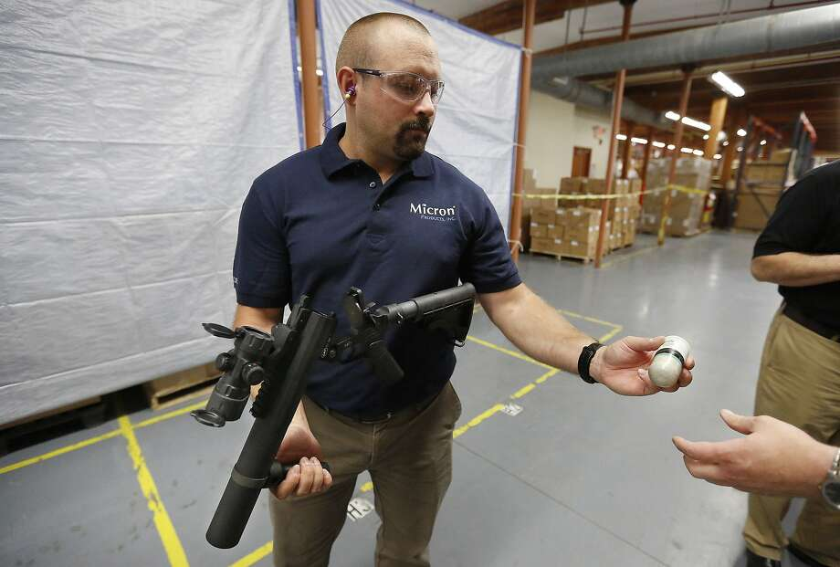 Chad Zrate of Micron Products Inc. prepares to demonstrate how the Fitchburg, Mass., firm's blunt impact projectiles work. Photo: Steven Senne, Associated Press