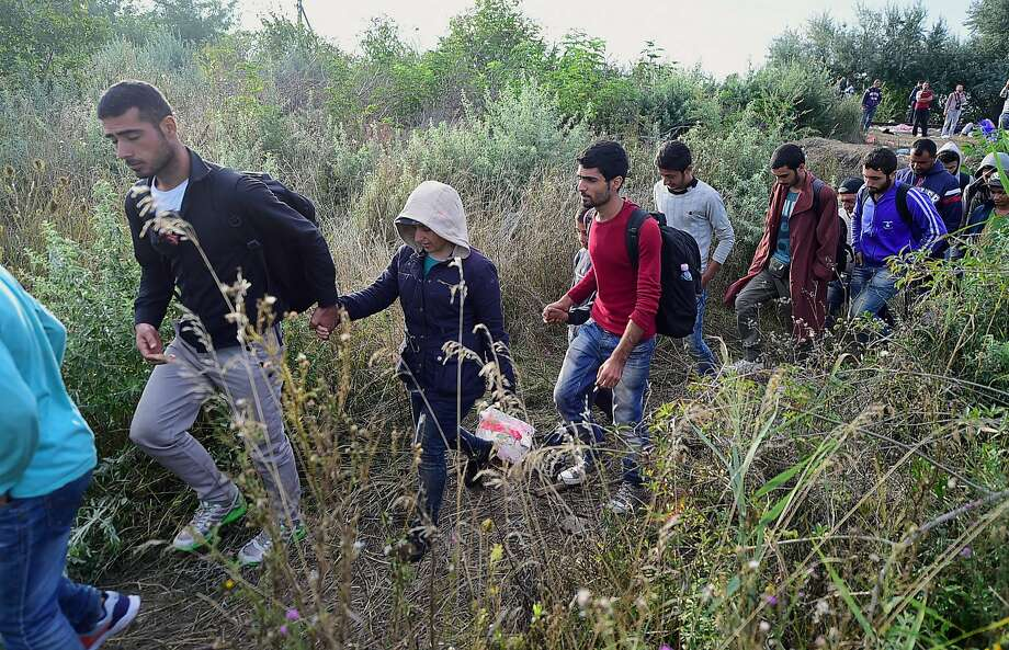 Migrants walk near the town of Roszke on the Hungarian-Serbian border. Nearly 10,000 migrants have crossed into Serbia in recent days with a plan to head into Hungary and on to Western Europe. Photo: Attila Kisbenedek, AFP / Getty Images