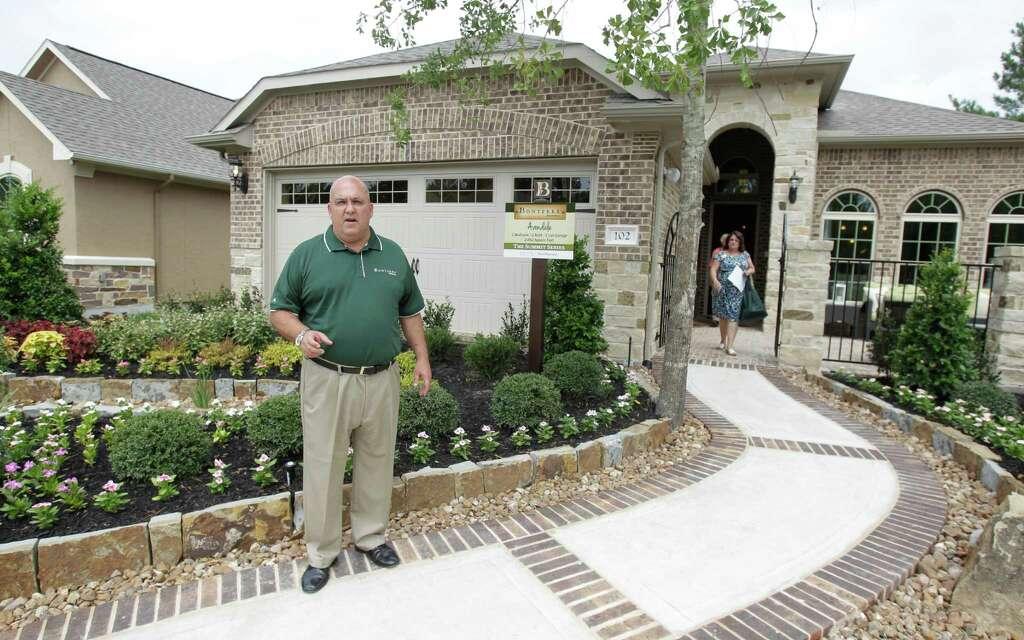 Jim Ellison, vice president of Tony Morrison sales and marketing, talks  outside a home