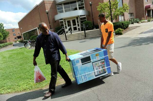 Antonie Brady of New York City, left, and his son Jason Brady, 13, carry a small fridge into the dorm of Antonie's daughter, freshman Roshaun Brady, 17, on Tuesday, Aug. 25, 2015, at Rensselaer Polytechnic Institute in Troy, N.Y. (Cindy Schultz / Times Union) Photo: Cindy Schultz / 00033121A