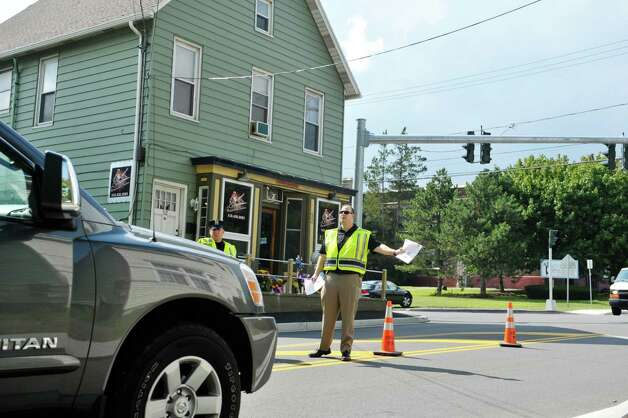 Colonie Police patrolman, Thomas Breslin, left, and investigator Jeff Lockart talk to motorists as members of the Colonie Police Department hand out fliers in front of Recycled Salon on Tuesday, Aug. 25, 2015, in Colonie, N.Y.  Jacquelyn Porreca was stabbed inside the business last week and died from her injuries, and police are looking to see if anyone traveling through the area last week saw anything.  (Paul Buckowski / Times Union) Photo: PAUL BUCKOWSKI / 00033127A