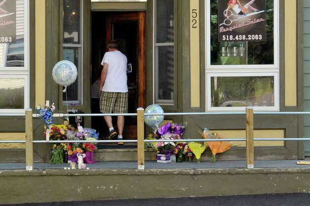 A man walks in to Recycled Salon past flowers on the front porch on Tuesday, Aug. 25, 2015, in Colonie, N.Y.  Jacquelyn Porreca was stabbed inside the business last week and died from her injuries, and police are looking to see if anyone traveling through the area last week saw anything.  (Paul Buckowski / Times Union) Photo: PAUL BUCKOWSKI / 00033127A
