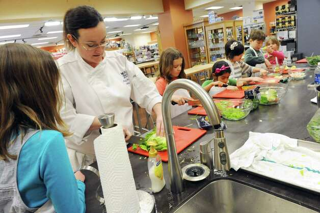 Guest chef Michelle Hines Abram teaches kids a California cuisine during a hands on Americana kids camp at Different Drummer's Kitchen Co. in Stuyvesant Plaza on Friday Feb. 22, 2013 in Guilderland, N.Y. The kids are from left, Claire Bender, 13 of Loudonville, Alycia Lee, 10 of Rexford, Isabella Giddings, 7 of West Sand Lake, Aiva Geracitan, 9, of Latham, Jonathan Seaver, 10, and Natalia Seaver, 7, of Scotia. (Lori Van Buren / Times Union) Photo: Lori Van Buren / 00021276A
