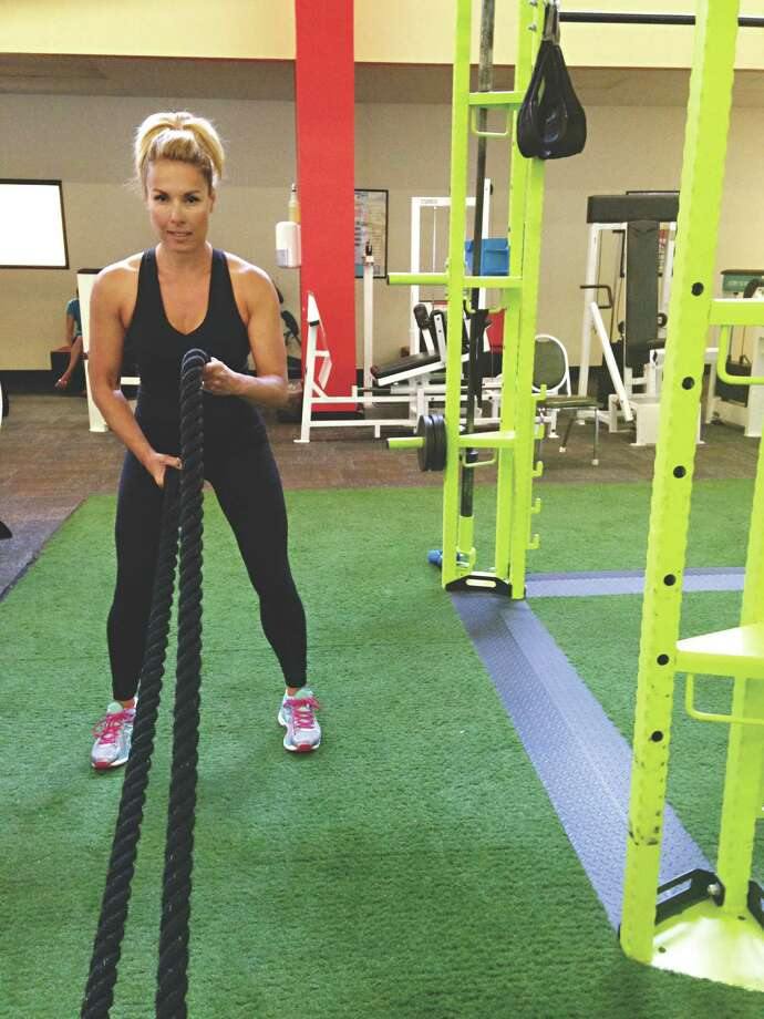 Teresa Burke, personal trainer at the HealthPlex in Clifton Park, demonstrates how to do alternating waves with battle ropes. (Carin Lane / Times Union)