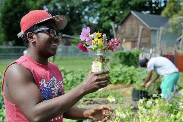 Amarie Sears, 17, creates a flower arrangement for his girlfriend in one of the lots owned by the Sanctuary for Independent Media, on Thursday, July 23, 2015, in Troy, N.Y.  The sanctuary has several lots that they are using to grow food and flowers.   (Paul Buckowski / Times Union) Photo: PAUL BUCKOWSKI / 00032644A