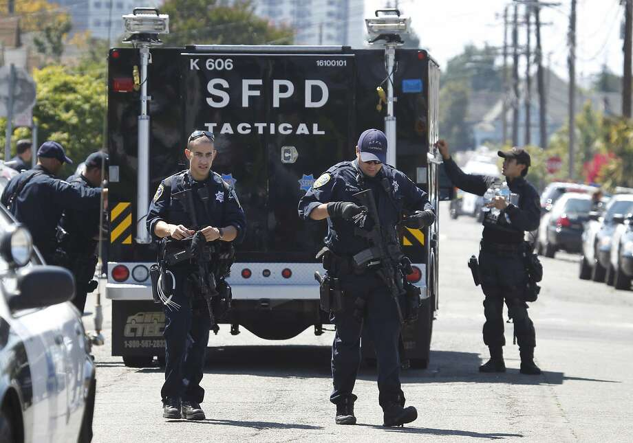 San Francisco police officers from the tactical unit walk to their vehicles in front of the Downs Memorial United Methodist Church on 61st Street near Idaho Street in Oakland, Calif. on Tuesday, Aug. 25, 2015 following a pursuit by San Francisco police officers of a suspect in a shooting near Jones and Lombard streets which extended across the Bay Bridge and ended on the streets of Oakland. Photo: Paul Chinn, The Chronicle