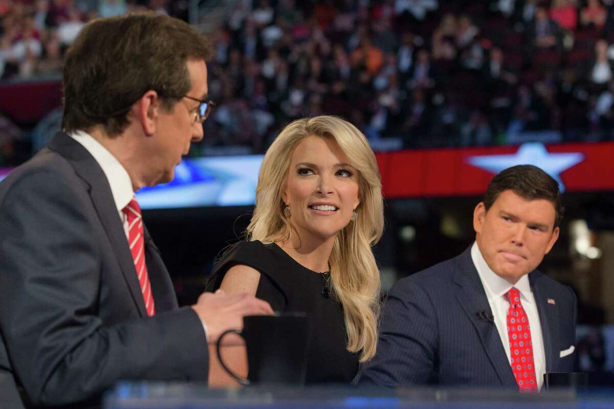 FOX News moderators Megyn Kelly, center, and Bret Baier, right, listens as Chris Wallace, left, beings introductions during the first Republican presidential debate at the Quicken Loans Arena Thursday, Aug. 6, 2015, in Cleveland. (AP Photo/John Minchillo)