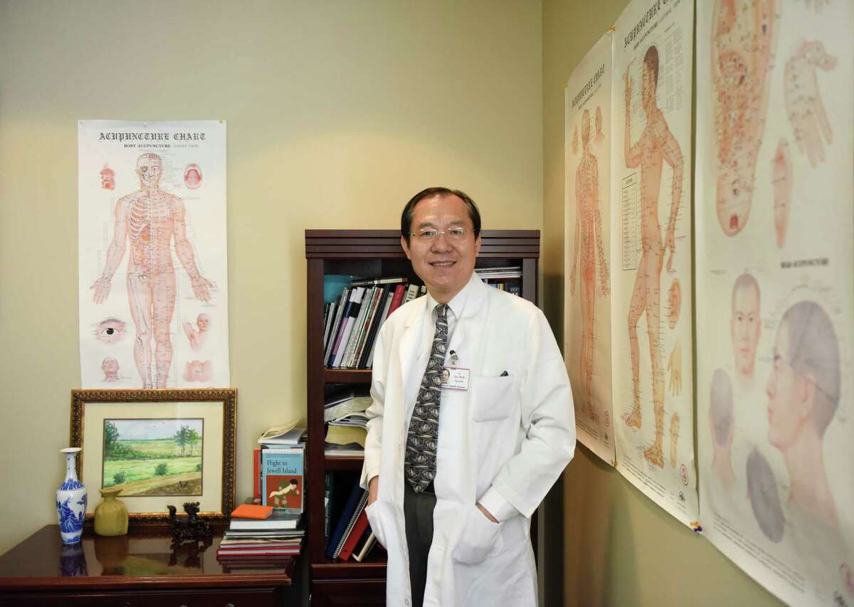 Dr. Jun Xu poses beside acupuncture charts in his office at Rehabilitation Medicine & Acupuncture Center in the Riverside section of Greenwich, Conn. Tuesday, Aug. 25, 2015. Dr. Xu offers acupuncture treatment for infertility, claiming that many patients have been successfully treated.