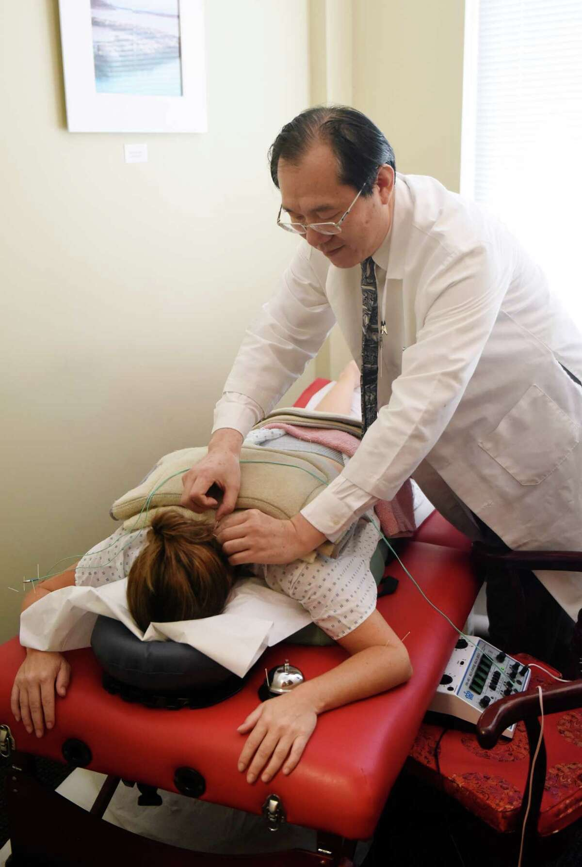 Dr. Jun Xu performs an acupuncture procedure on a patient at Rehabilitation Medicine & Acupuncture Center in the Riverside section of Greenwich on Tuesday. Xu offers acupuncture treatment for infertility, claiming that many patients have been successfully treated.