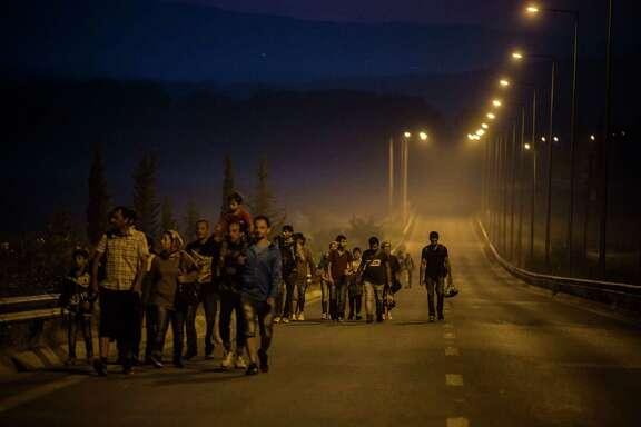 Syrian refugees walk along the roads of the border town of Idomeni, northern Greece, to cross the border and enter Macedonia on Tuesday. With the help of smartphones and social media, many migrants are making their journeys without paying traffickers to guide them.