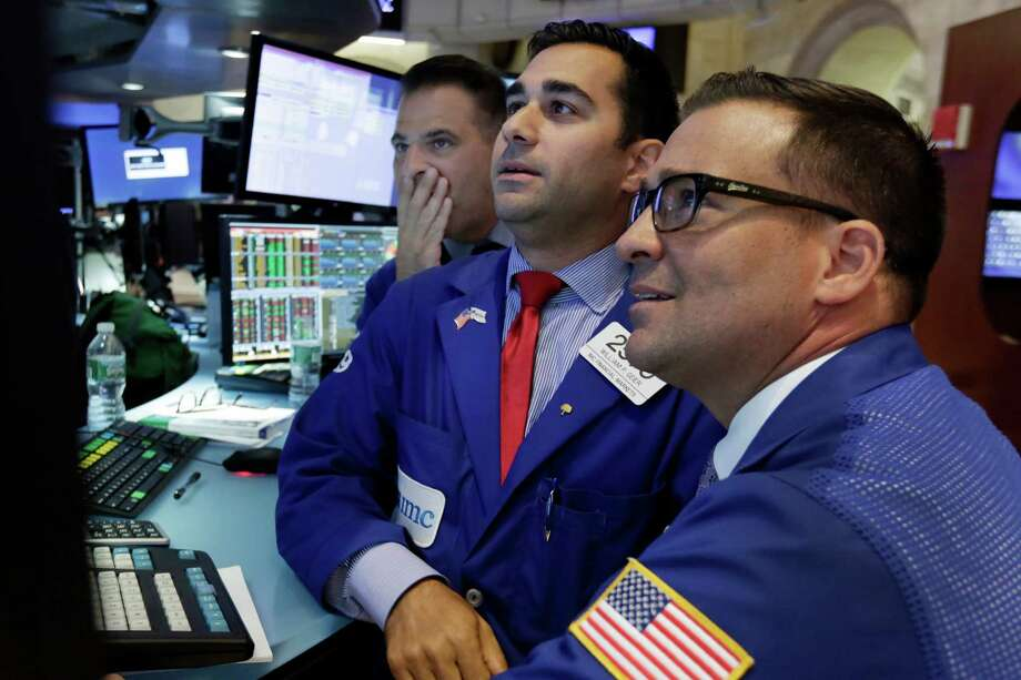 Specialists gather Tuesday on the floor of the New York Stock Exchange. The Dow finished 1.3 percent lower. Photo: Richard Drew /Associated Press / AP