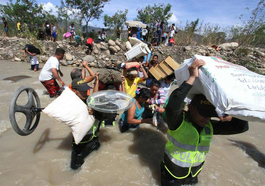 Colombian police help carry people's household belongings across the Tachira River from Venezuela, top, to Colombia, on the border that separates San Antonio del Tachira, Venezuela from Villa del Rosario, Colombia, Tuesday, Aug. 25, 2015, during a mass exodus of Colombians. Venezuelan President Nicolas Maduro vowed to extend a crackdown on illegal migrants from neighboring Colombia he blames for rampant crime and widespread shortages, while authorities across the border struggled to attend to droves of returning deportees. Photo: Eliecer Mantilla, Associated Press