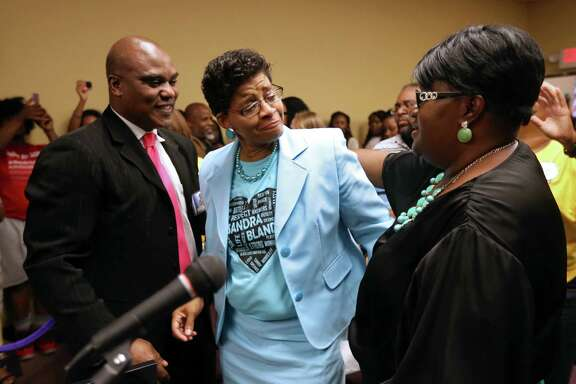 Geneva Reed-Veal, center, of Chicago, mother of Sandra Bland, shown with attorney Cannon Lambert, left, and Rev. Lenora Dabney, of Hope A.M.E. Church, react after city council members voted in favor of the approval to name a portion of University Drive to Sandra Bland Parkway at a Prairie View City Council meeting in the city council chamber at city hall Tuesday, Aug. 25, 2015, in Prairie View, Texas. The city council passed a proposal and resolution to name a portion of University Drive to be named Sandra Bland Parkway. Sandra Bland pulled over for failing to signal a lane change later committing suicide by hanging herself in her Waller County Jail cell with a plastic garbage bag on July 13, 2015.