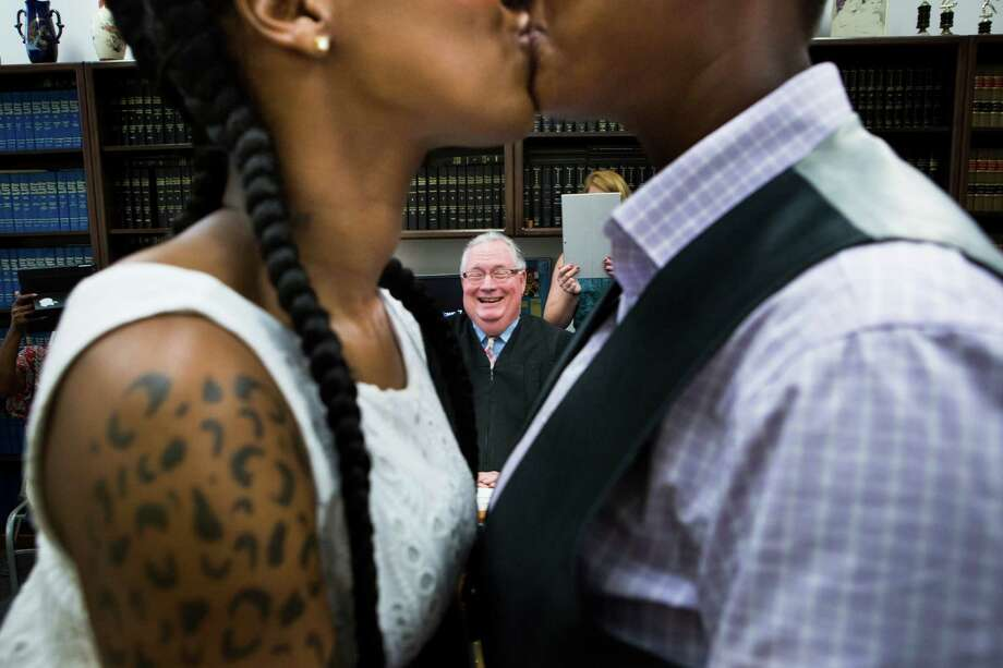 Erikka Givens, left, and Hattie Givens, right, share a kiss after Judge Dale Gorczynski, center, pronounce them wife and wife. Photo: Marie D. De Jesus, Staff / © 2015 Houston Chronicle