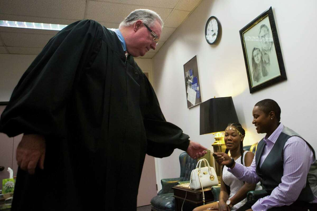 Judge Dale Gorczynski gives Hattie Givens his business card with his name and number so she can pass it on to other same-sex couples looking to get married and not finding a judge that would perform the ceremony. Friday, Aug. 21, 2015, in Houston.
