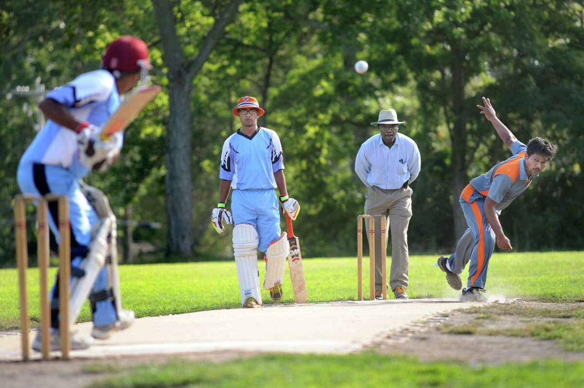 Albany Highlanders' bowler Ashok Adikooppula, right, releases the ball during their semifinal cricket game against Uprising on Saturday, Aug. 22, 2015, at Grout Athletic Field in Schenectady, N.Y. Uprising batters are Amit Dinaram, left, and Gavin Narine center. (Cindy Schultz / Times Union)