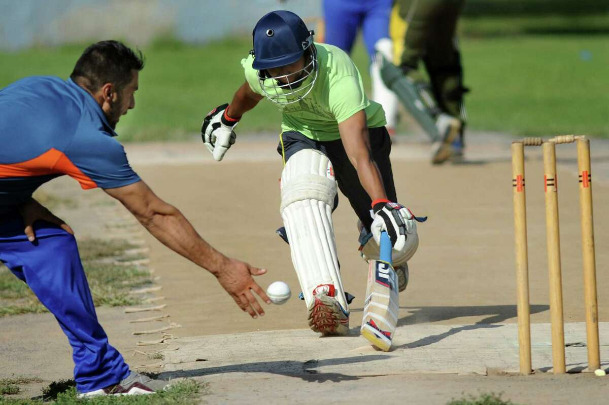Tri-City's Munish Jagmohan, center, beats out Excelsior's Javed Safi during their semifinal cricket game against Uprising on Saturday, Aug. 22, 2015, at Grout Athletic Field in Schenectady, N.Y. (Cindy Schultz / Times Union)