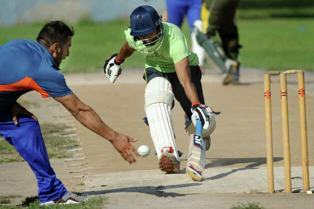 Tri-City's Munish Jagmohan, center, beats out Excelsior's Javed Safi during their semifinal cricket game against Uprising on Saturday, Aug. 22, 2015, at Grout Athletic Field in Schenectady, N.Y. (Cindy Schultz / Times Union) Photo: Cindy Schultz / 00033027A
