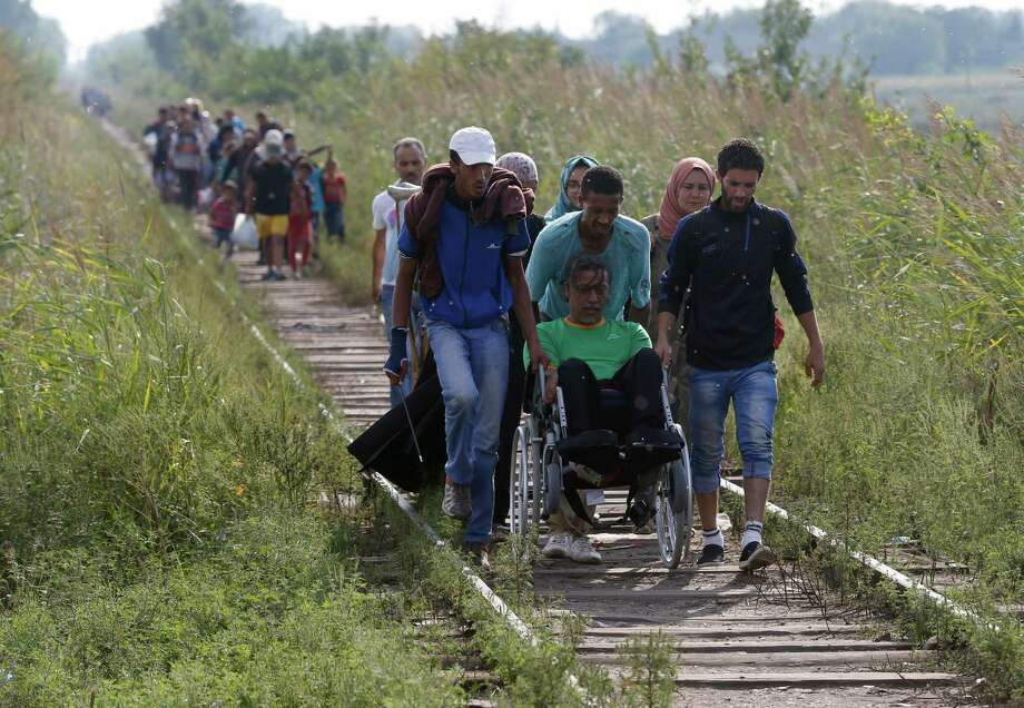 Migrants assist a wheelchair user as they all advance along the railway track near the Serbian border with Hungary, near Horgos, Serbia, Tuesday, Aug. 25, 2015. Thousands of migrants have been crossing into Hungary on their way toward Germany and other rich EU countries as part of a new wave of people fleeing war-thorn countries of the Middle East and Africa. (AP Photo/Darko Vojinovic) ORG XMIT: XDMV123 Photo: Darko Vojinovic / AP