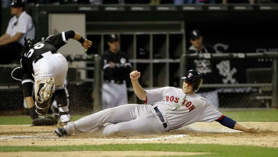 Boston Red Sox's Josh Rutledge scores past Chicago White Sox catcher Geovany Soto on a double by Mookie Betts, as the throw from Chicago White Sox shortstop Alexei Ramirez is wide of the plate, during the third inning of a baseball game Tuesday, Aug. 25, 2015, in Chicago. (AP Photo/Charles Rex Arbogast) ORG XMIT: CXS110 Photo: Charles Rex Arbogast / AP