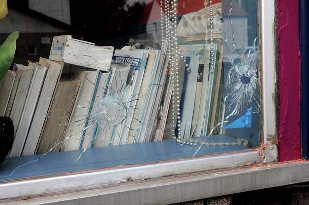 Bullet holes are seen in the window of a store on the corner of 112th St. and Fifth Ave. on Tuesday, Aug. 25, 2015 in Lansingburgh, N.Y.  A shoot-out between Troy police officers, Joshua Comitale and Chad Klein and 39-year-old Thaddeus Faison of Albany took place Saturday night. Faison was shot repeatedly near the intersection of 112th Street and Fifth Avenue by at least one of the officers and was later pronounced dead at St. Mary's Hospital. (Lori Van Buren / Times Union) Photo: Lori Van Buren / 00033124A