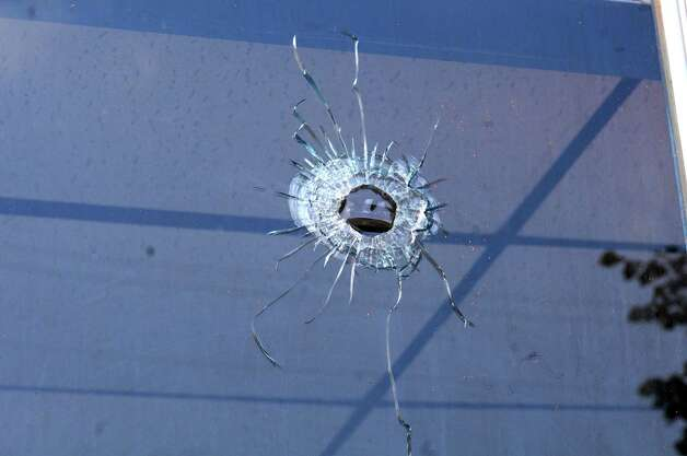 A bullet hole is seen in the window of a store on the corner of 112th St. and Fifth Ave. on Tuesday, Aug. 25, 2015 in Lansingburgh, N.Y.  A shoot-out between Troy police officers, Joshua Comitale and Chad Klein and 39-year-old Thaddeus Faison of Albany took place Saturday night. Faison was shot repeatedly near the intersection of 112th Street and Fifth Avenue by at least one of the officers and was later pronounced dead at St. Mary's Hospital. (Lori Van Buren / Times Union) Photo: Lori Van Buren / 00033124A
