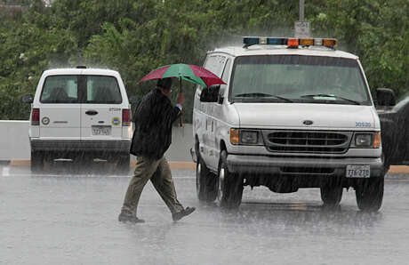 An unidentified man walks across the parking lot at the Houston City Hall Annex as rain showers move through the area Tuesday, Aug. 25, 2015, in Houston.
