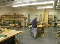 A member of the Darien Senior Center repairs a kitchen chair in the center's woodshop on Aug. 25, 2015. Members of the center who are skilled with the equipment frequently undertake repairs of furniture for little or no money, or create signs for trails, and scenery for the Darien Arts Center.