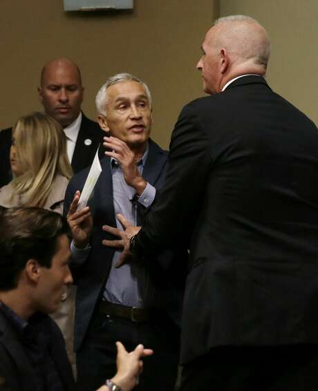 A security guard (right) kicks Uni vision an chor Jorge Ramos out of a Donald Trump news con ference. Photo: Charlie Neibergall, Associated Press