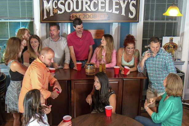 "Source ""Fun Committee"" members chat around the bar in the company's pub, McSourceley's."