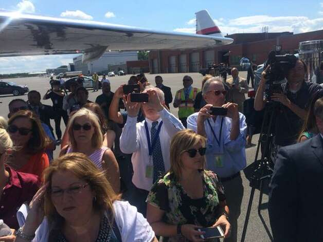 Reporters and others gather near the plane that brought Triple Crown winner American Pharoah and thoroughbred Funny Cide to Albany International Airport on Wednesday. American Pharoah is running in Saturday's Travers Stakes. (Will Waldron / Times Union)