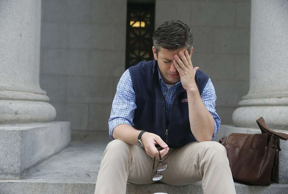 Phillip McCarthy sits on the steps of the old Pacific Coast Stock Exchange building in San Francisco, Calif. on Wednesday, Aug. 26, 2015. Stock prices showed an early rise when the markets opened for trading. Photo: Paul Chinn, The Chronicle