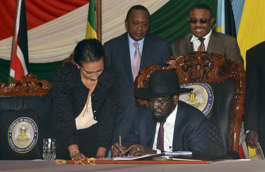 South Sudan President Salva Kiir signs a peace deal as Kenya's President Uhuru Kenyatta (center) and Ethiopia's Prime Minister Hailemariam Desalegn look on in the capital city of Juba. Photo: Jason Patinkin, Associated Press