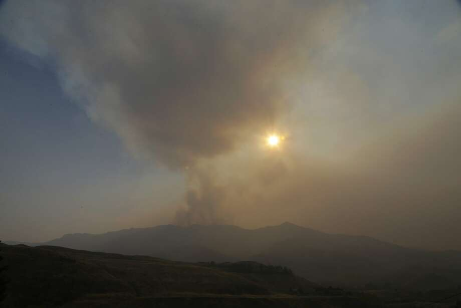 Smoke from a wildfire near Pateros, Wash., partially obscures the sun on Tuesday. The hazy conditions grounded helicopters and airplanes that had been fighting the blazes. Photo: Ted S. Warren, Associated Press