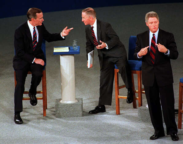 President Bush, left, talks with independent candidate Ross Perot as Democratic candidate Bill Clinton stands aside at the end of their presidential debate in Richmond, Va., Oct. 15, 1992. Photo: MARCY NIGHSWANDER, AP / AP