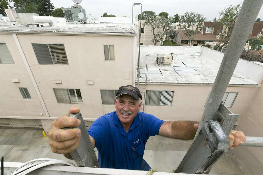 Roofer Chuck Jewett with Hull Brothers Roofing & Waterproofing climbs a ladder to check on his workers' progress resurfacing the roof of townhomes at the Marina del Rey seaside community of Los Angeles on Tuesday, Aug. 25, 2015. While drought-plagued California is eager for rain, the forecast of a potentially Godzilla-like El Nino event has communities clearing out debris basins, urging residents to stock up on emergency supplies and even talking about how a deluge could affect the 50th Super Bowl. (AP Photo/Damian Dovarganes) Photo: Damian Dovarganes, Associated Press