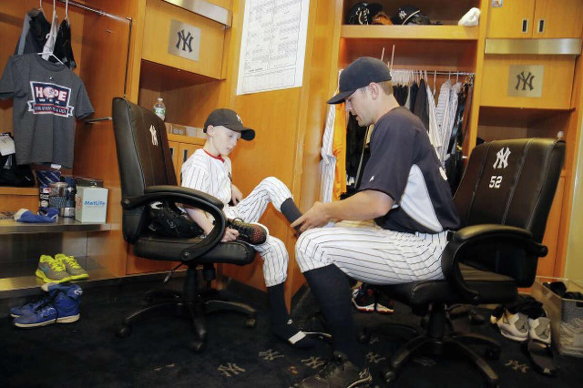 Yankees closer David Robertson helps HOPE Week honoree Sean Callahan to get ready for Wednesday night's game.