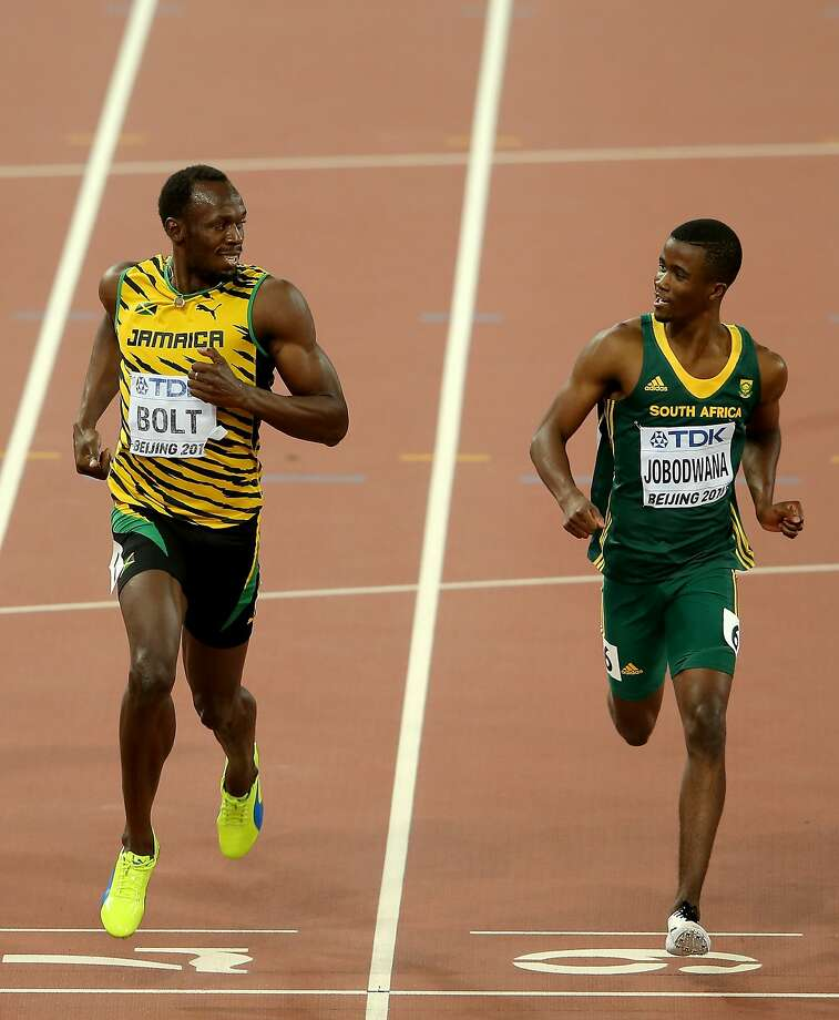 Jamaica's Usain Bolt (left) and South Africa's Anaso Jobodwana keep track of each other in a 200 meters semifinal. Photo: Lintao Zhang